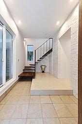 明るく広々とした玄関ホール。純白の天然石と上質な床の大盤タイルに当社の建物らしい品格を感じる事が出来ます。すっきりとした印象を与えるスチール階段には、挿し色としてウオールナット無垢の段板を設えました。
