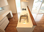 I型のキッチンと配膳台、そして勝手口、という人気の高い対面キッチンです。収納量もたっぷりと、コミ箱の置き場や食品庫なども用意されています。 (125号地)