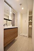 木目調扉が美しい洗面台。縦に配置したLED照明により顔に影を作りません