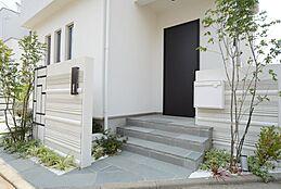 閑静な住宅街で、前面道路も幅がゆったりございます。玄関前は植栽や、小窓を沢山施すことでデザイン性の高いアプローチになっています。お客様のお好みに合わせてコーディネート致します。/当社施工例