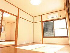 リフォーム後写真DK横の洋室です。壁天井のクロスを張り替え、床を張りました。照明も新品に交換しました。掃き出しの窓があり採光のよいお部屋です。