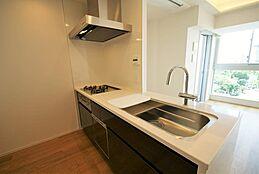 ダイニングを望む広々とした最新のキッチン。うれしい食器洗浄乾燥機付きで家事をサポートします。