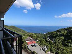 景色:バルコニー左側よりみた景色。正面には青い空と海、深緑の緑が美しい山々うを望む。