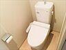 ウォシュレット機能付きのトイレ。上部には吊戸棚があり、トイレットペーパーのストックや掃除用具を収納するのに役立ちます。また、ペーパーホルダーは標準装備されています。